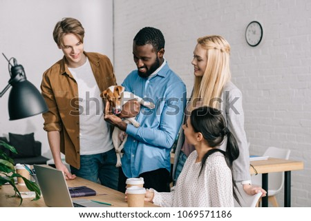 african american businessman holding jack russell terrier and smiling colleagues standing near