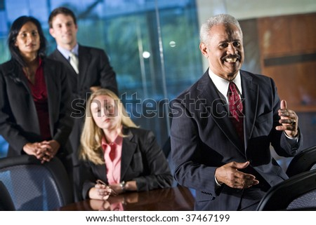 African American businessman in boardroom with colleagues standing behind him