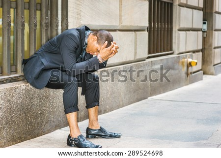 African American businessman in New York. Dressing in black suit, tie, leather shoes, wearing wristwatch, young black guy sitting on window on street, bending back, hands covering head, tired, sad. - stock photo