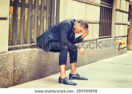African American businessman in New York. Dressing in black suit, tie, leather shoes, young black guy sitting on window on street, a hands covering head, looking at wristwatch.  Instagram effect. - stock photo
