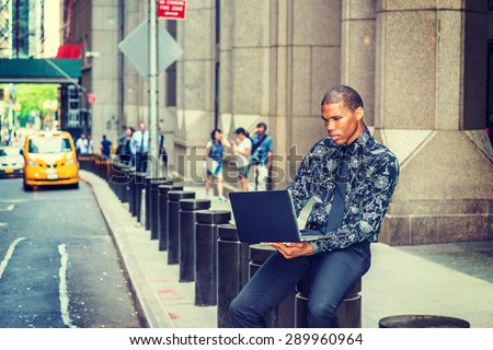 African American businessman in New York. Wearing black flower patterned shirt, tie, young guy siting on street, reading, working on laptop computer. Yellow cab, people on background. Instagram effect - stock photo