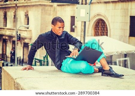 African American businessman in New York. Wearing black shirt, tie, light green pants, leather shoe, young black guy siting outside office, reading, working on laptop computer. Instagram effect. - stock photo