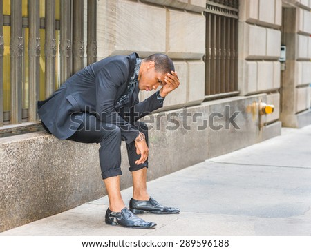 African American businessman in New York. Wearing black suit, tie, leather shoes, wristwatch, young black guy sitting on window on street, bending back forward, hand touching forehead, sad, thinking. - stock photo