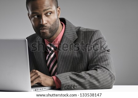 African American Businessman Looking Suspicious While Working On His Laptop
