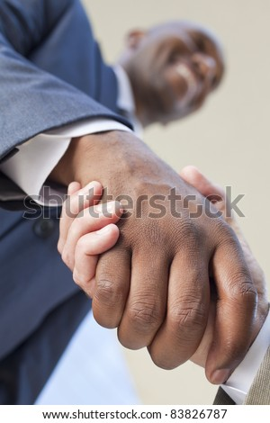 African American businessman or man shaking hands with a caucasian colleague doing a business deal - stock photo