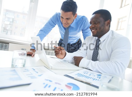 African-american businessman pointing at laptop screen while explaining project to his colleague - stock photo