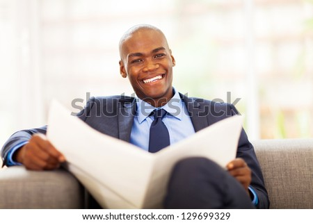 african american businessman reading newspaper on sofa