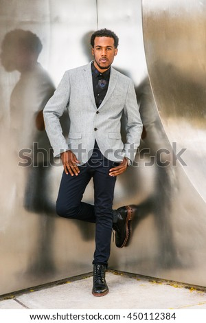 African American Businessman Semi-Formal Fashion in New York. Wearing gray blazer, dark blue pants, black leather boot shoes, a guy with beard standing in corner of metal silver wall, thinking. - stock photo