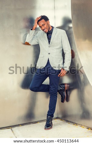 African American Businessman Semi-Formal Fashion in New York, wearing gray blazer, dark blue pants, black leather boot shoes, standing in corner of metal silver wall, hand touching head, thinking. - stock photo