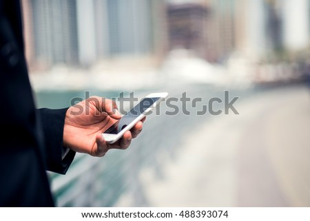 African american businessman sending a message on a phone.