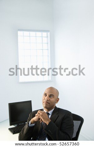 African American businessman sitting at office desk looking off in the distance. - stock photo