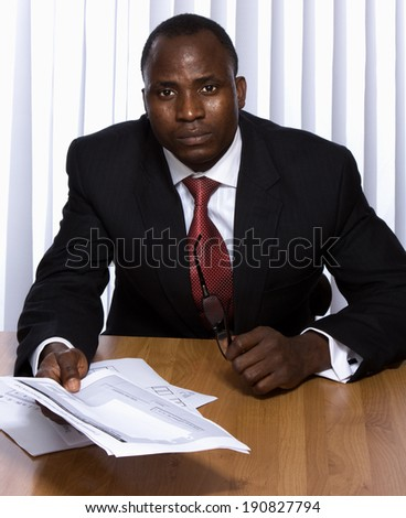 African American businessman sitting on the desk with documents - stock photo