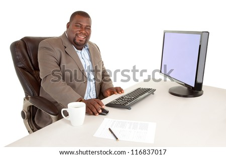 African American Businessman Smiling at the Camera While Sitting at his Desk