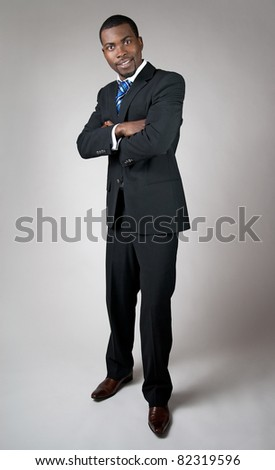 African American businessman standing with his arms crossed, smiling.