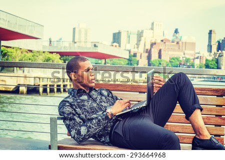 African American businessman traveling in New York. Wearing black flower patterned shirt, pants, young black guy sitting on chair by East River, reading, working on laptop computer. Instagram effect. - stock photo