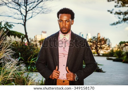 African American Businessman traveling in New York. Wearing woolen overcoat, pink shirt, bow tie, wristwatch, young black man with beard standing at park in sunset, looking at you. Winter Fashion.  - stock photo