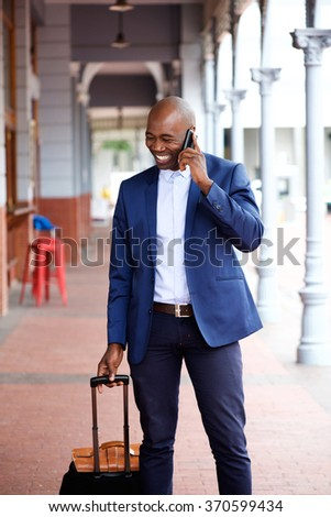 African american businessman traveling with bag and talking on mobile phone  - stock photo