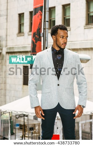 African American Businessman traveling, working in New York. Wearing gray blazer, black pants, young black man with beard standing on Wall Street, confident, successful. Instagram filtered effect.  - stock photo