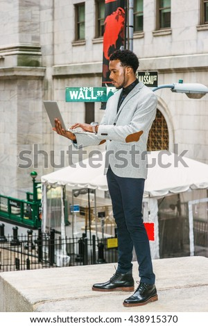 African American businessman traveling, working in New York. Wearing gray blazer, black pants, leather boot shoes, a black man with beard standing on street, reading, working on laptop computer. - stock photo