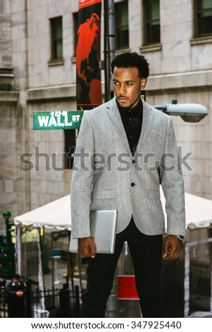 African American Businessman traveling, working in New York. Wearing gray blazer, holding laptop computer, a black man with beard standing on Wall Street, looking away. Instagram filtered look.  - stock photo