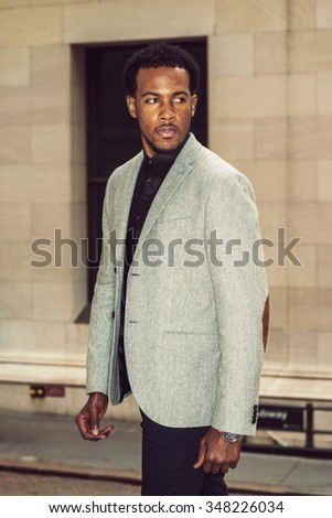 African American Businessman traveling, working in New York. Wearing gray patterned blazer,  a young black professional with beard standing on street, tensely looking away. Instagram filtered look.  - stock photo