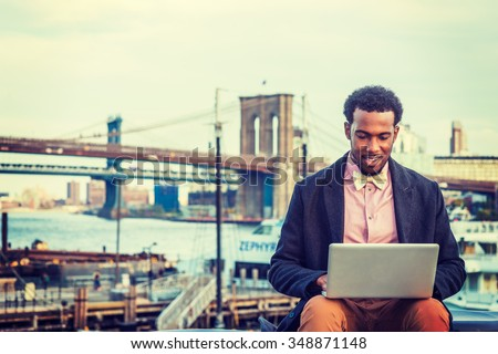 African American Businessman traveling, working in New York, wearing woolen overcoat, pink shirt, bow tie, sitting by East River, working on laptop computer. Brooklyn bridge, boat on background  - stock photo