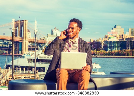 African American Businessman traveling, working in New York, wearing woolen overcoat, pink shirt, bow tie, sitting on bench at harbor, working on laptop computer, talking on phone in same time.  - stock photo