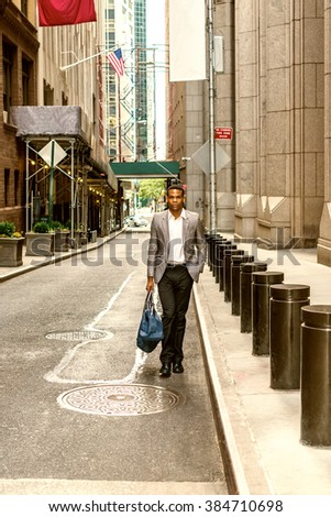 African American Businessman traveling, working in New York. Young black man walking on narrow old street with high buildings, carrying blue bag. Car running on background. Color filtered effect.  - stock photo
