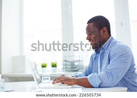 African-american businessman typing on laptop in office - stock photo