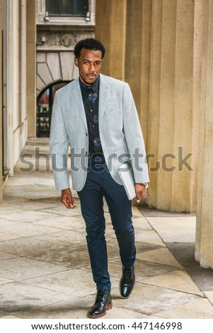 African American Businessman with beard working in New York, wearing gray blazer, blue pants, black leather boot shoes, carrying laptop computer, walking into vintage office building, going to work.  - stock photo