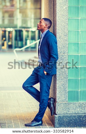 African American businessman working in New York. Wearing blue suit, leather shoes, a young black guy standing against wall on street, looking up, sad, deeply thinking. Instagram filtered look.  - stock photo