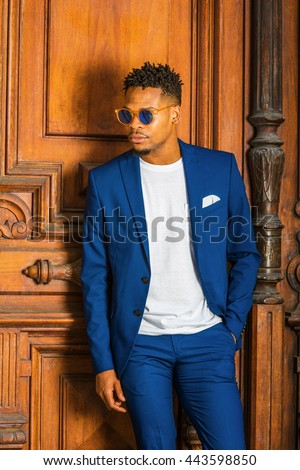 African American Businessman working in New York. Wearing blue suit, unbuttoned, white T shirt, blue sunglasses, college student with little goatee, standing by vintage doorway, looking down, thinking - stock photo