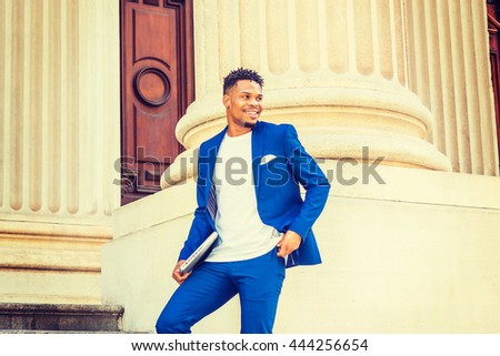 African American Businessman working in New York. Wearing blue suit, white T shirt, college student with little goatee, standing by vintage doorway on campus, carrying laptop computer, smiling. - stock photo