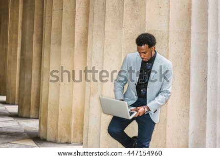 African American businessman working in New York. Wearing gray blazer, blue pants, guy standing against columns outside office, looking down, reading, working on laptop computer during work break. - stock photo