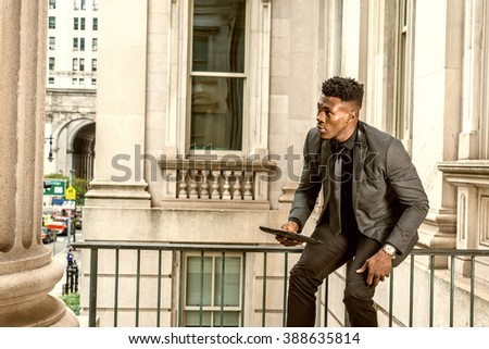 African American Businessman working in New York, wearing jacket, black necktie, sitting on railing in office building, holding tablet computer, getting up, looking around, distracted while reading.  - stock photo