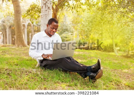 african american businessman working on laptop outdoors - stock photo