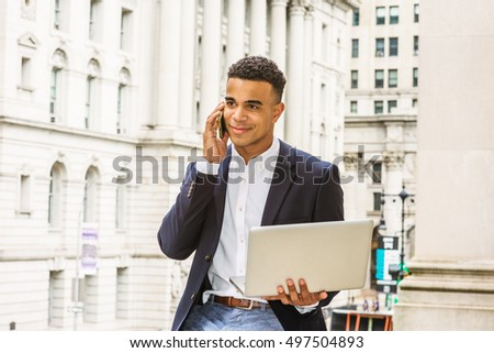 African American Businessman works in New York. Wearing black blazer, white shirt, young man sits on street by vintage office building, works on laptop computer, talks on cell phone. Filtered effect.