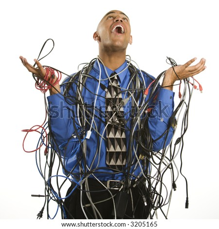 African American businessman wrapped in computer cables looking up with exasperation. - stock photo