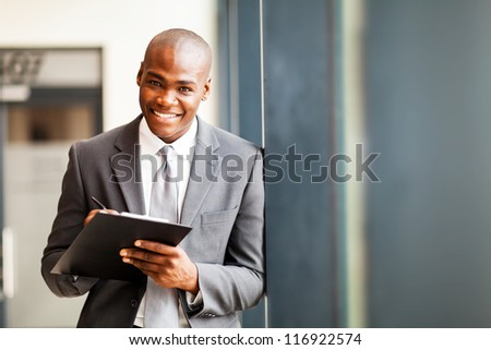 african american businessman writing report in office - stock photo