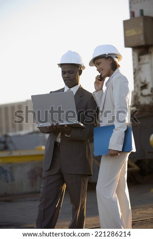African American businesspeople wearing hardhats - stock photo
