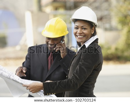African American businesspeople with blueprints - stock photo