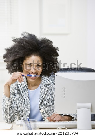 African American businesswoman biting on pen - stock photo