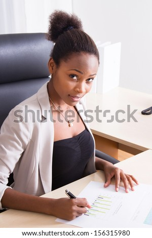 African American businesswoman sitting by her desk in the office.  - stock photo
