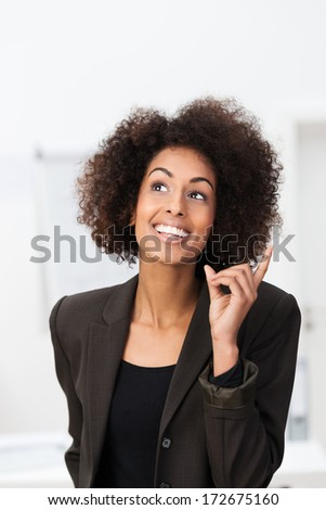 African American businesswoman with a bright idea smiling with glee and raising her finger as she has a brainwave and realizes the solution to a problem - stock photo