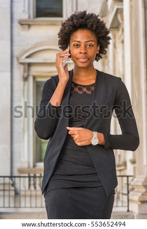 African American Businesswoman with short afro hairstyle working in New York, wearing fashionable work clothes, wristwatch, stands in office building, talking on cell phone.