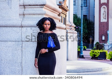 African American Businesswoman working in New York. Wearing long sleeve, off shoulder dress, carrying bag under arm, a lady with braid hairstyle standing on street. Filtered look with purple tint. - stock photo