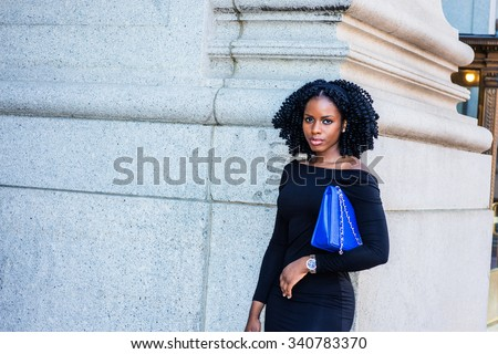 African American Businesswoman working in New York. Wearing long sleeve, slim off shoulder dress, carrying blue bag under arm, young black lady standing on street. Filtered look with dark blue tint.  - stock photo