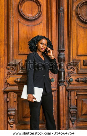 African American Businesswoman working in New York. Young black female lawyer with braid hairstyle standing by vintage style law firm doorway, carrying laptop computer, seriously listening cell phone. - stock photo