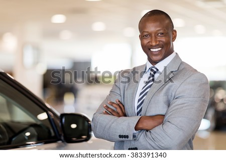 african american car dealership principal standing in vehicle showroom - stock photo