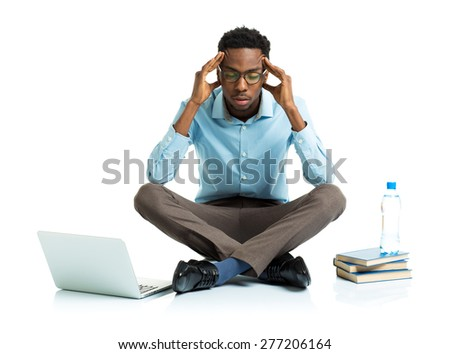 African american college student in stress sitting with laptop, books and bottle of water on white background - stock photo